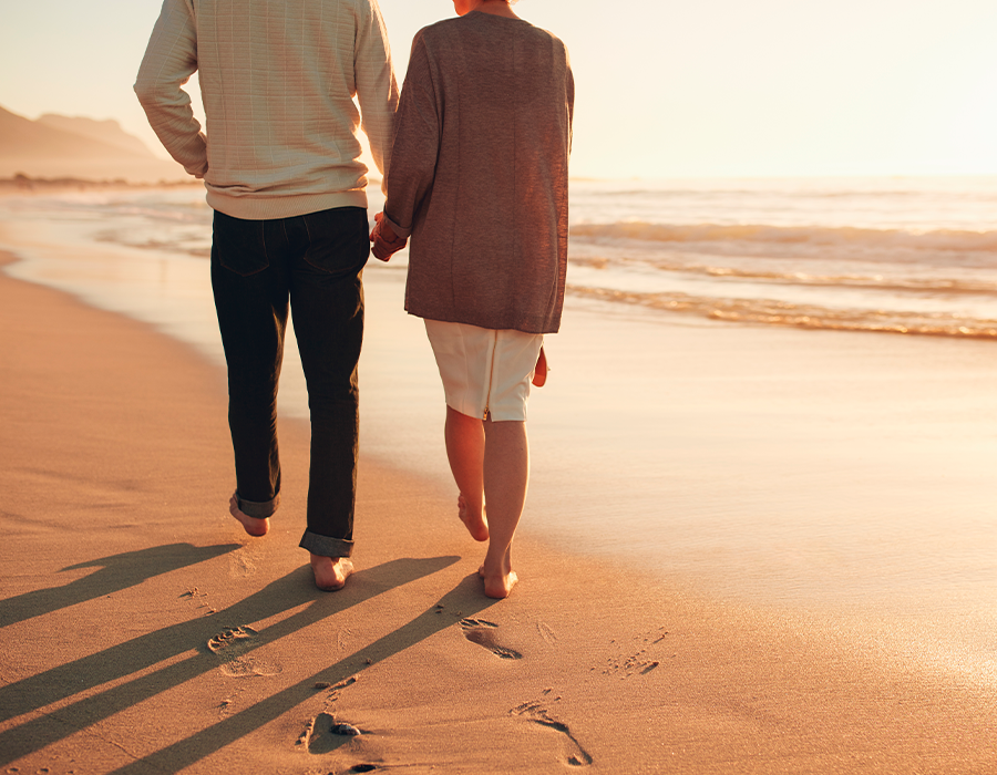 Senior couple holding hands walking on the beach enjoying the sunset.